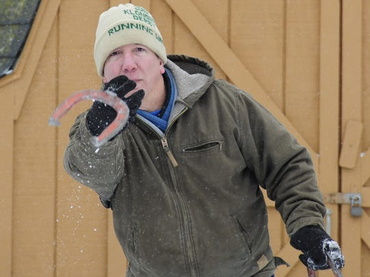 Rick Brehmer pitches a horseshoe during the 35th annual Pink Elephant Snowshoe tournament in Smiths Creek.