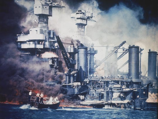 A small boat rescues a USS West Virginia crew member from the water after the Japanese bombing of Pearl Harbor, Hawaii, on Dec. 7, 1941, during World War II. Two men can be seen on the superstructure, upper center. The mast of the USS Tennessee is beyond the burning West Virginia. AP A small boat rescues a USS West Virginia crew member from the water after the Japanese bombing of Pearl Harbor, Hawaii on Dec. 7, 1941 during World War II. Two men can be seen on the superstructure, upper center. The mast of the USS Tennessee is beyond the burning West Virginia. (AP Photo)