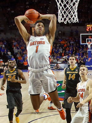 Florida Gators forward Devin Robinson (1) slam dunks the ball over Missouri Tigers guard Jordan Geist (15) as Gators guard Canyon Barry (24) and Tigers forward Reed Nikko (14) and forward Kevin Puryear (24) look on during the half of an NCAA basketball game at Exactech Arena at the Stephen C. O'Connell Center. The Gators won 93-54.