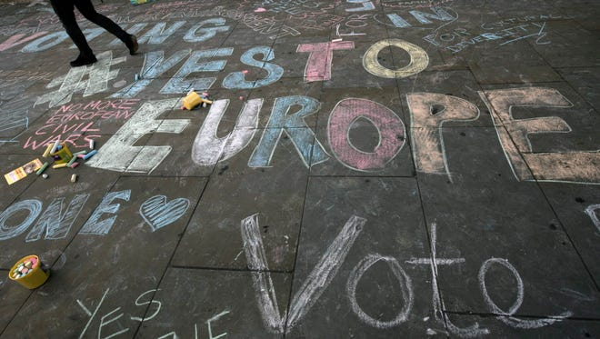Members of the public write support slogans on a sidewalk as they take part in a 'Remain In' Rally in Trafalgar Square, Central London, Britain, 21 June 2016.