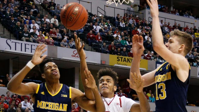 Indiana forward Juwan Morgan chases after a loose ball against Michigan guard Kameron Chatman, left, and forward Moritz Wagner, right, on March 11, 2016.