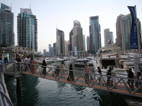 In this April 1, 2015 photo, tourists and visitors cross a bridge to get on their dhow cruise at the Marina water canal as a tram crosses on a bridge in Dubai, United Arab Emirates. That waterfront is finally coming into its own after years of seemingly endless construction work. (AP Photo/Kamran Jebreili)
