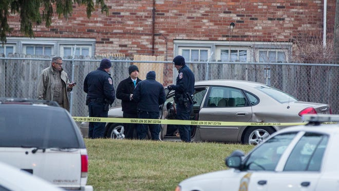 Homicide detectives and IMPD officers gather around a tan Ford Taurus in the 4400 block of Park Forest Court where a man was found shot dead Wednesday.