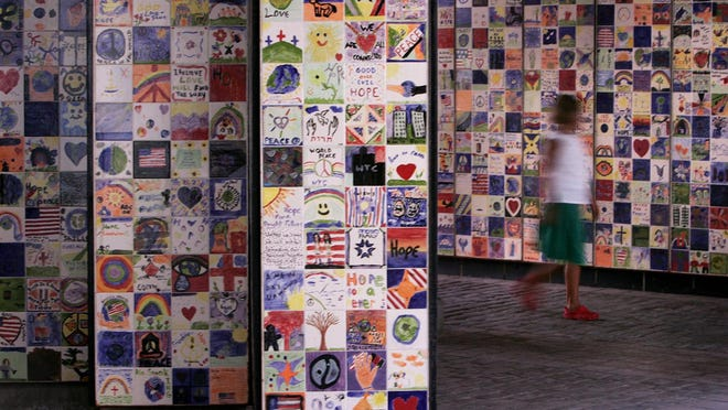 "A girl walks past a wall of tiles on the way to Waterplace Park in Providence in 2006, part of the installation ""Wall of Hope -- A Rhode Island Community Response to September 11."""