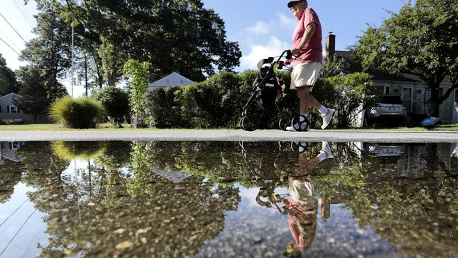 Brad Hathaway, 88, is reflected on a puddle on North Road in Mattapoisett, as he goes for his daily walk nearing his goal of 24,901 miles of walking since he began in 1988. Mr. Hathaway who was recently diagnosed with Parkinson's, is attempting to walk the Earth's circumference while trying to raise money for the Mattapoisett Land Trust in an effort to preserve the land surrounding Aucoot Cove in Mattapoisett.