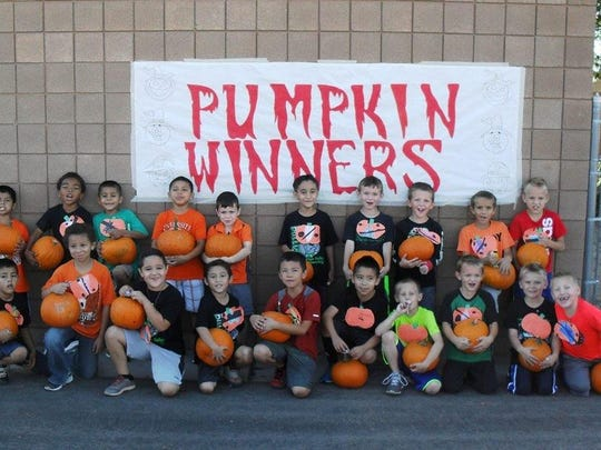First grade students hold their winning pumpkins after