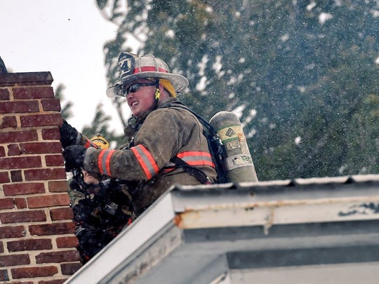 Despite strong winds and snow, firefighters take to the roof of a two-story home in Hopewell Township.