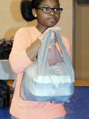 Volunteer Saniya Woods brings up takeout plates during Thursday's community dinner.
