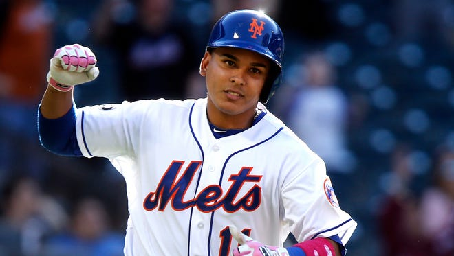 The Mets' Ruben Tejada celebrates on his way to first base after hitting a game-winning single in the 11th inning against Philadelphia on Sunday.