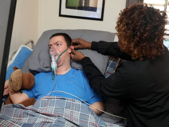 Carlene Beard, an LPN, administers a nebulizer while providing treatment for Tristen Shackelford at his home on February 16, 2018.