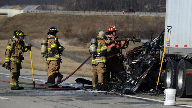 Firefighters spray down the cab of a semi on U.S. 33 north of Ohio 188 Monday afternoon, Feb. 29, 2016, in Greenfield Township. According to Ohio Highway Patrol Trooper Lori Dixon, the driver of the semi, Melvin P. Nihart Jr., was driving north on the highway when he smelled smoke in the vehicle's cab. Nihart, 63, from Wilmington, pulled the truck over a little more than a mile north of the Ohio 188 overpass and saw flames coming from the engine compartment. Dixon said he tried to put the fire out with extinguishers he had on the truck, but the fire was too intense. Firefighters from Hocking and Greenfield township fire departments were able to put the truck out. The Fairfield County Emergency Management Agency and hazardous materials teams were called to scene to check for runoff from the semi into a nearby ditch. EMA Director is Jon Kochis said the runoff was mainly diesel fuel and that the Ohio Environmental Protection Agency had been called to check the ditch for contaminates. Dixon said she hoped to have the passing lane of the highway open soon, but the shoulder and right lane would remain closed until the semi could be removed.
