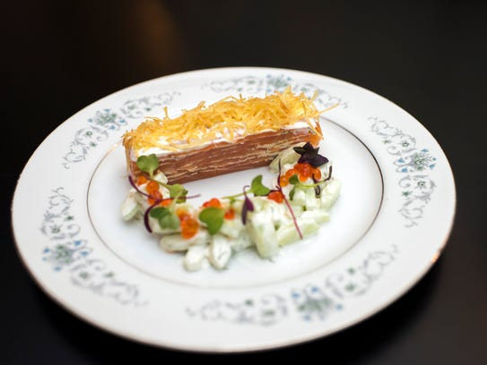 The Smoked Salmon Pavé, ribbons of silky fish layered with salmon mousse, represent the surf in a meal at Royal Boucherie. Threads of crispy potato offer textural contrast to the smoothness of the fish and the soft crunch of an accompanying salad of cucumber and chervil, dressed with crème fraîche and briny pops of roe.
