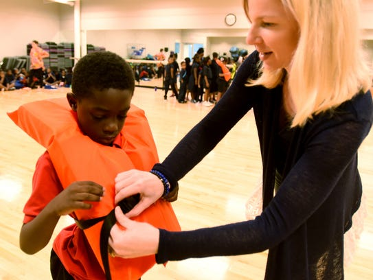 Alison Cate helps Jalen Hill with a life jacket at