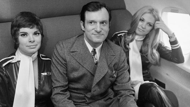 Seated in rear-of-plane bedroom, Hugh Hefner, the old bunny master himself, center, sits on newly created jet, Tuesday, Feb. 17, 1970, Chicago, Ill. Dubbed the Hare Jet, $5,500,000 plane was given press view before taking Playboy promoter amid plush interiors to Los Angeles, Calif. The women are unidentified. (AP Photo/Edward Kitch)