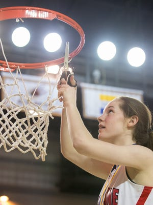 Sophomore Maggie Connolly clips her piece of the net after Ursuline downed Sanford 39-34 for the Raiders' 16th state title in the DIAA Girls Basketball Tournament on Friday at the Bob Carpenter Center.