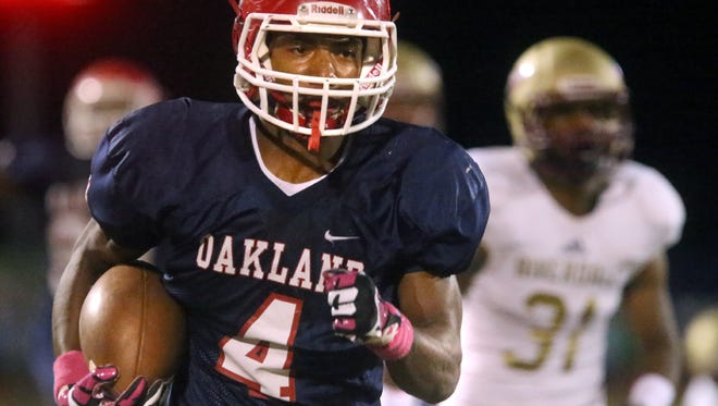 Oakland's Lazarius Patterson (4) runs the ball down the sidelines to score a touchdown as Riverdale's Kentrell Green (31) tries to catch Patterson at Oakland Friday, Oct. 16, 2015.
