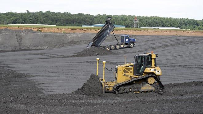 Heavy equipment dumps and spreads coal ash in a landfill at Asheville Regional Airport in this 2014 photograph. Erosion problems were found at the site recently.