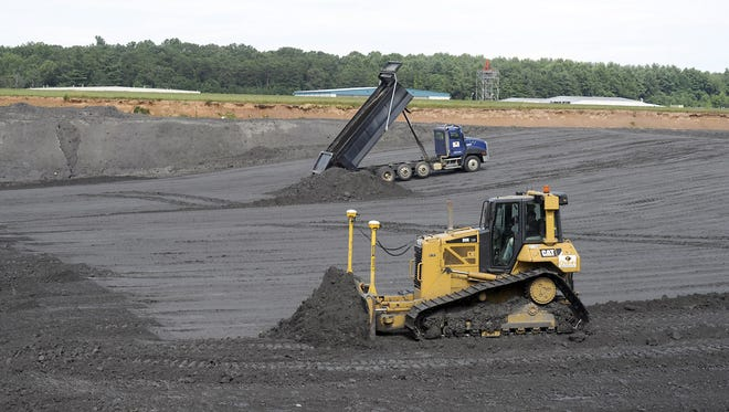 In this 2014 file photo, heavy equipment dumps and spreads coal ash in a landfill at Asheville Regional Airport.