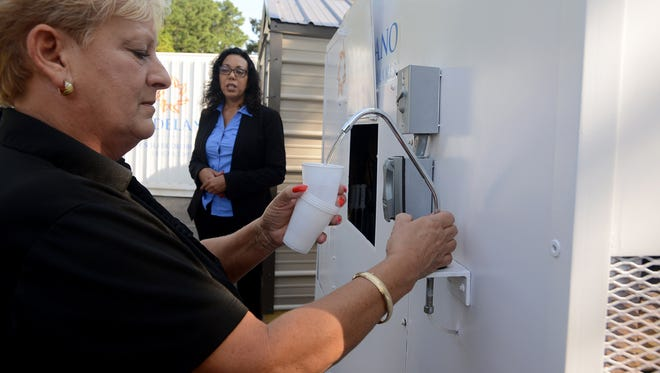 Aldelano HR manager Sheila Wilson dispenses water from one of Aldelano's Solar WaterMaker units. The unit produces up to 50 gallons of water that is made from the humidity in the air.