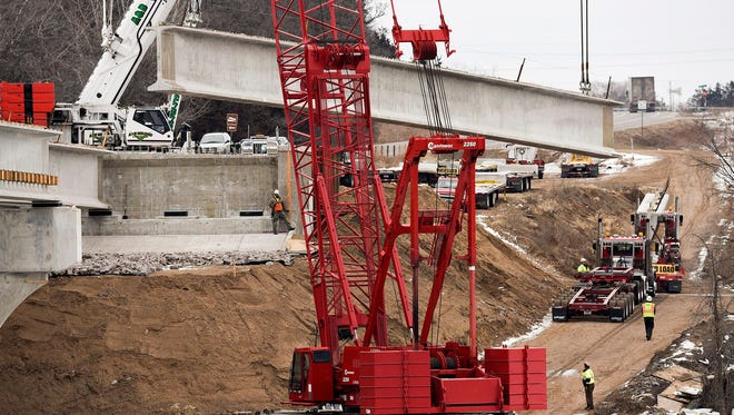 A large concrete beam weighing 220,000 pounds is lifted into place on the new Minnesota Highway 24 bridge over the Mississippi River in Clearwater earlier this year.