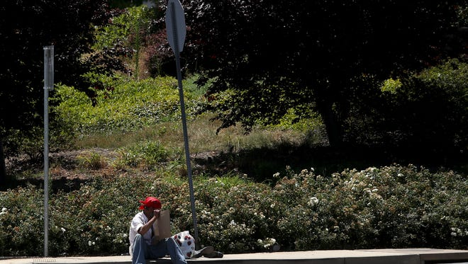 """A man sits with a sign Thursday near Walmart in Anderson. New signsinAnderson remind panhandlers not to be """"aggressive,"""" and Redding is also thinking up more ways to bar similar behavior."""