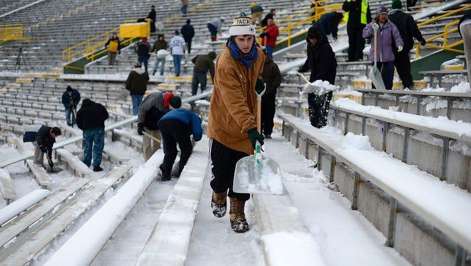Sammy Lett, of De Pere, shovels snow at Lambeau Field on Saturday, Nov. 29, 2014.