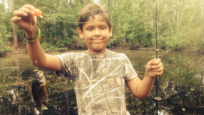Isaac Perez, son of Daily Advertiser news director Kristin Askelson, proudly holds up a fish he caught two years ago at age 9 during a hunting and fishing trip near DeRidder.