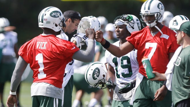 Jets quarterbacks Michael Vick, left, and Geno Smith fist-bump at training camp  in Cortland on July 24.