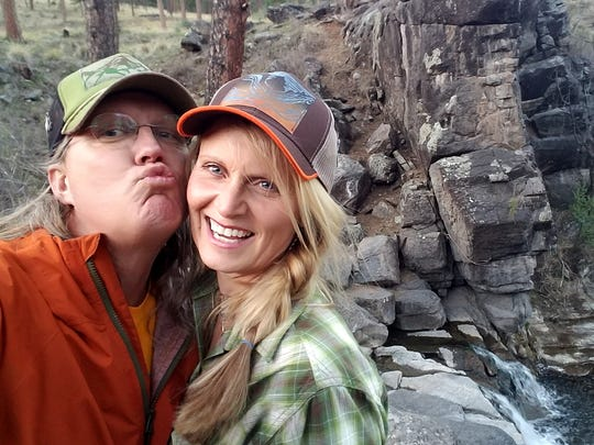 Rich Dozier tries to steal a kiss from his wife Anna while taking a picture of themselves during a hike on Eagle Creek Trail.