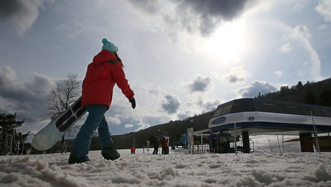 Christie Stanzione, Henrietta, heads to a lift as snow clouds close in as she snowboards at Bristol Mountain in Ontario County on Feb. 9, 2016.