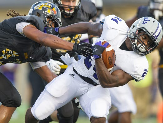 Ben Davis High School senior Dorian Tate (24) works to break free of the grasp of Avon High School junior Brody Gude (43) during the first half of action. Avon High School hosted Ben Davis High School in varsity football Friday, August 29, 2014.