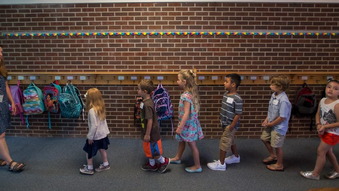 Kindergarten teacher Ms. Shedd leads her students down the hall to go to recess on the first day of school at O'Dea Elementary School, Wednesday, August 23, 2017, in Fort Collins, Colo.