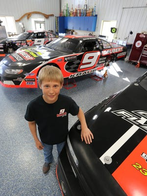 Derek Kraus stands among his trophies and the family's racing vehicles at the Kraus's garage near Stratford.