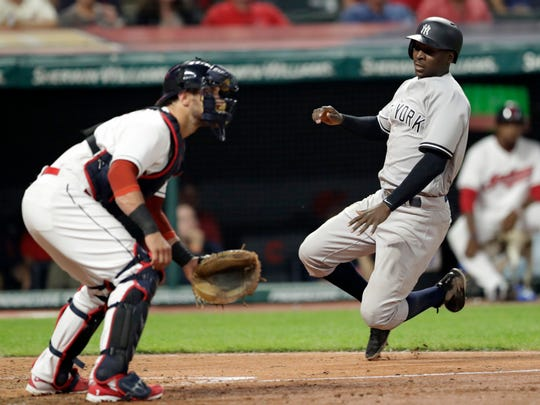 New York Yankees' Didi Gregorius scores as Cleveland Indians' Yan Gomes waits for the ball during the eighth inning of a baseball game Thursday, July 12, 2018, in Cleveland.