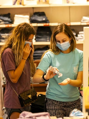 Shoppers adjust their masks and apply hand sanitizer while shopping in the Paddock Mall.