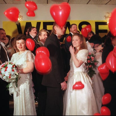 Heart balloons fall from the ceiling as couples participating