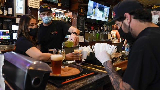 In this May 29, 2020, file photo, Jessica Ciaramitaro, Daryn Feenstra and Nicholas Soriano mix drinks while wearing face masks at the bar at San Pedro Brewing Company in the San Pedro area of Los Angeles. California will allow schools, day camps, bars, gyms, campgrounds and professional sports to begin reopening with modifications starting Friday, June 12, 2020.