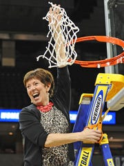 Muffet McGraw cuts down the rest of the net after Notre