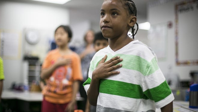 Des Moines second-grader Jayden Delerme says the Pledge of Allegiance on the first day of school in this 2015 Register file photo. The Waukee school board has directed staff to have high school students say the pledge at least once a week.