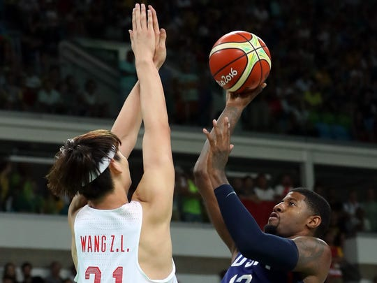 Aug 6, 2016; Rio de Janeiro, Brazil; United States guard Paul George (13) shoots the ball against China center Zhelin Wang (31) in the men's basketball group A  preliminary round during the Rio 2016 Summer Olympic Games at Carioca Arena 1.