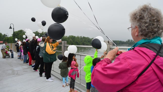 Community members on Saturday prepare to release balloons in memory of the victims of the May 3 shooting on the Trestle Trail bridge.