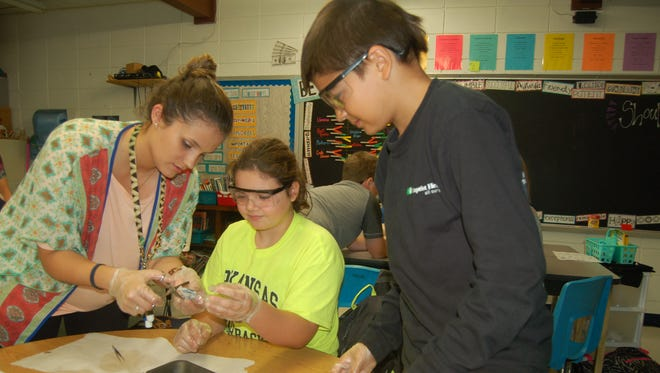 Sixth-grade science and social studies teacher Maggie Davenport (left) helps Katelynn Benedict (middle) and Michael Lynn dissect a cow eyeball Wednesday at Cotter. Students learn how light penetrates the eye and the similarities between a cow's eye and the human eye.