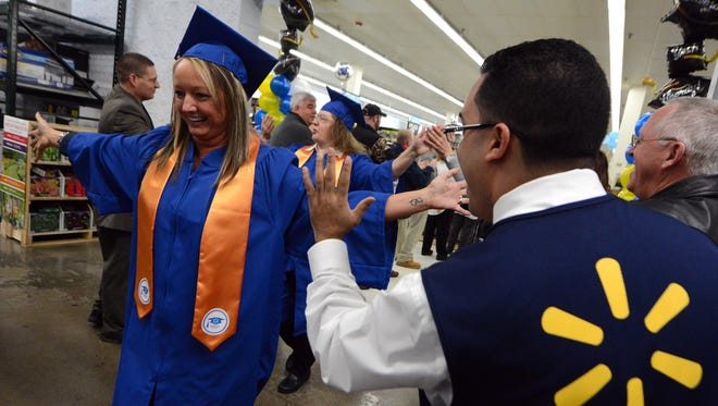 One of the first graduates from the first Wal-Mart Academy in Pennsylvania, Victoria Amandola, claims supervisor, gets a high-five as  she and her classmates head to commencement, Thursday, March 2, 2017.  John A. Pavoncello photo