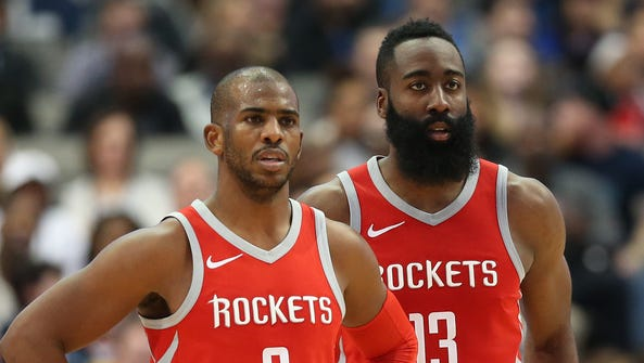 Chris Paul and James Harden look on during a break