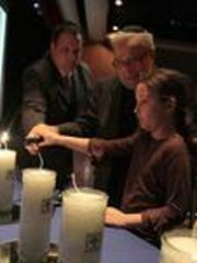 From left, Meyer Muschel helps his father, Nachum Muschel, and daughter, Cayla, light a candle in honor of his family at the Yom Ha'Shoah Tribute Program at Rockland Community College in Suffern on April 22, 2012.