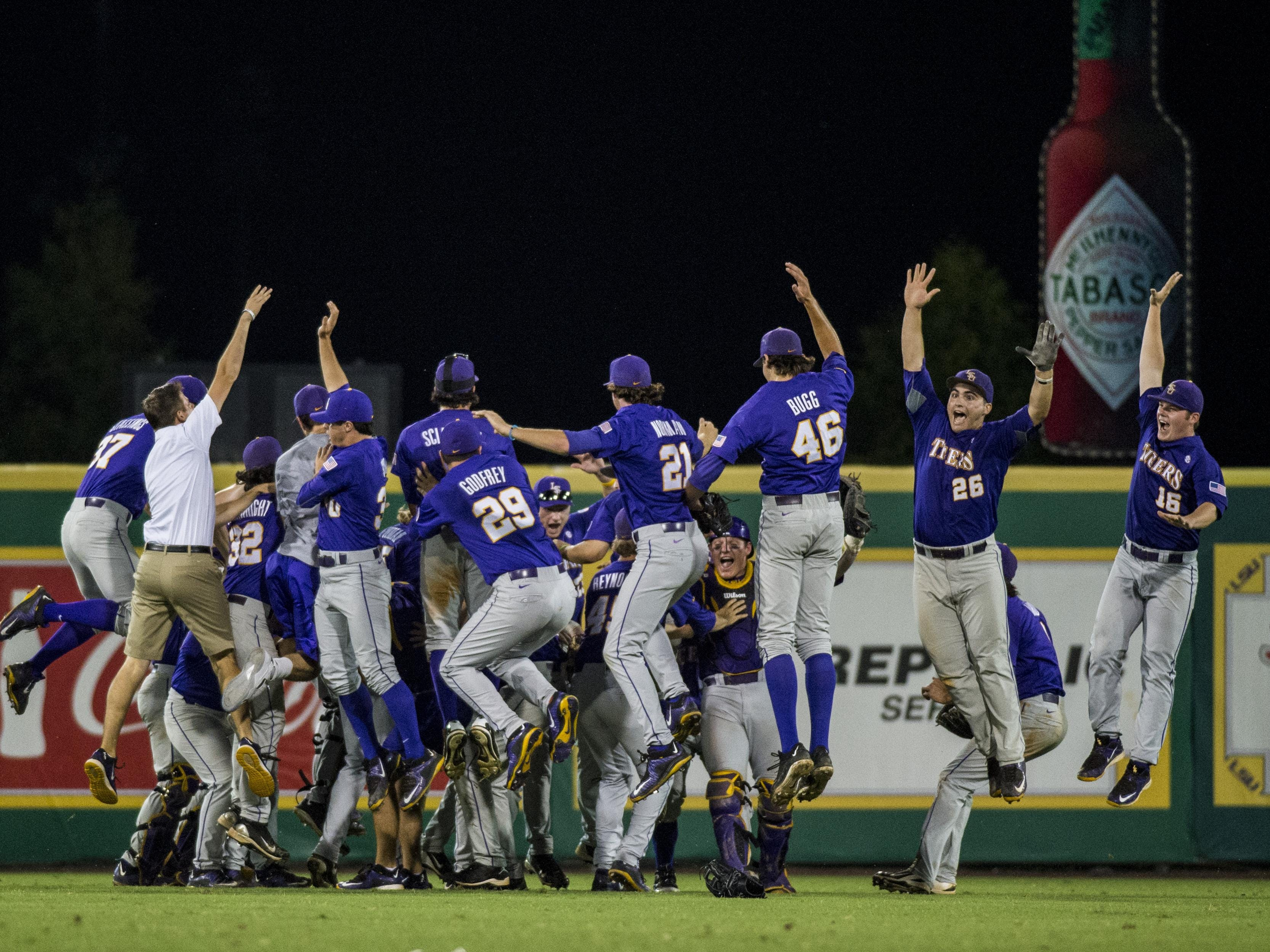 LSU players leap in celebration in the outfield following their 6-3 victory over the UL Ragin' Cajuns in an NCAA Super Regional game at Alex Box Stadium in Baton Rouge on Sunday.