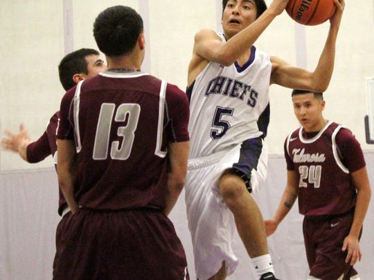 Mescalero's Aloysius Comanche drives toward the basket.