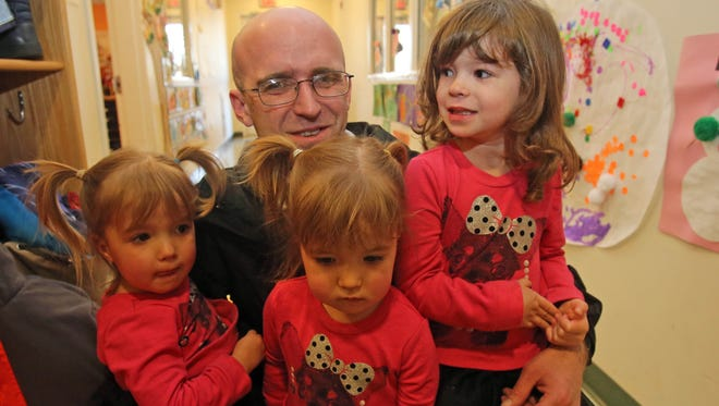 Daniel Greeley with his three daughters: twins, Amelia and McKenna, 2, and  Avery, 4, at Rockland Community College's childcare center in Ramapo. Greeley uses the childcare center so he can keep studying to become a nurse.