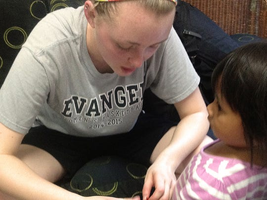 Evangel University junior Alison Jarrell works with a child at an orphanage in Manila, Phillipines.