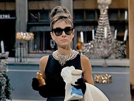 "With a croissant and take-out coffee a spectacularly dressed Audrey Hepburn enjoys ""Breakfast at Tiffany's."""